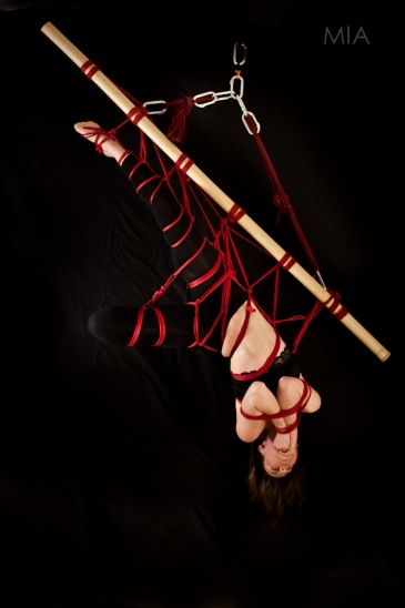 Girl upside down in rope and bamboo