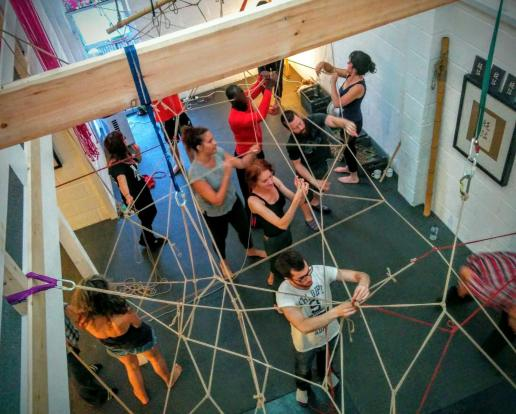 People tying a giant rope mesh in the studio